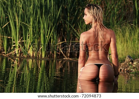 A blonde bikini model posing against a setting sun on a body of water - stock photo