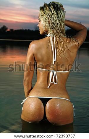 A blonde bikini model posing against a setting sun on a body of water - stock photo