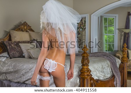 A blonde bride poses in lingerie in a home environment