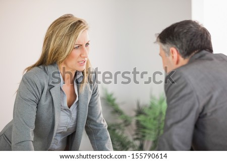 A blonde businesswoman getting angry with a businessman - stock photo