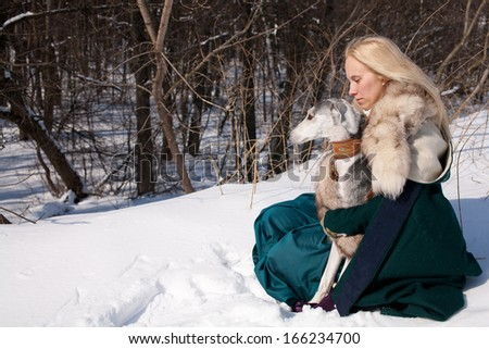 A blonde girl and a grey saluki on snow  - stock photo