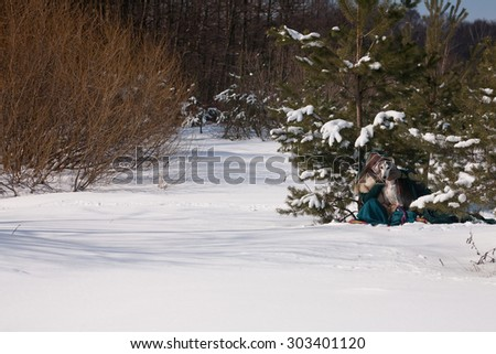 A blonde girl and a saluki on snow forest