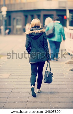 A blonde girl is walking in the street with a black leather bag with her hand. She is wearing black clothes and white shoes. Image has a vintage effect applied.