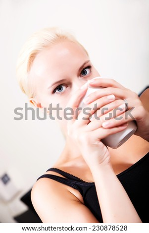 A blonde girl relaxing on a Sofa drinking a cup coffee