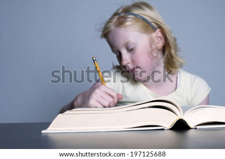 A blonde girl writing something in a book.