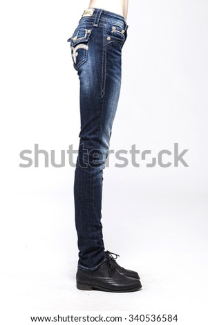 A blonde hair woman(girl, model) stand up wearing blue denim jean(pants, trousers) with black Military Shoes side view isolated white. - stock photo
