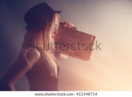 A blonde hipster girl is listening to a vintage gold boombox radio with a speaker for a music entertainment concept.