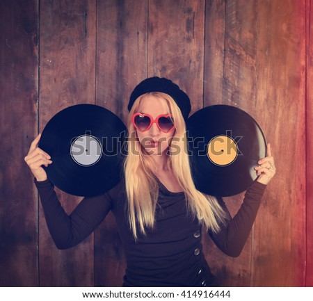 A blonde hipster girl with glasses is holding two vintage vinyl record for a music entertainment concept.