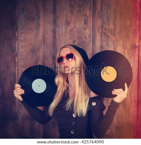 A blonde hipster girl with glasses is holding vintage vinyl records for a music, dj or entertainment concept.