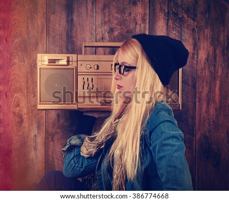 A blonde hipster girl with glasses is listening to  a vintage gold boombox radio with a speaker for a music entertainment concept.