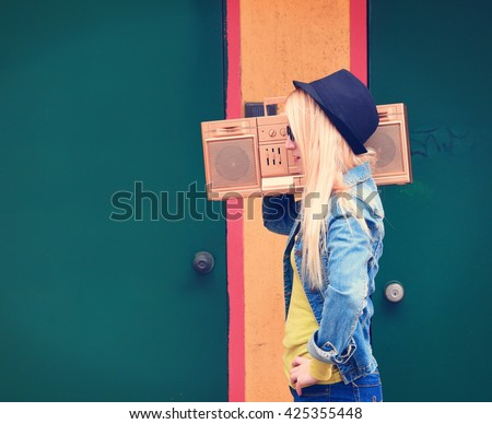A blonde hipster girl with glasses is listening to a vintage gold boombox radio with a speaker for a music entertainment concept. - stock photo