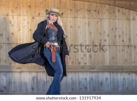 A blonde model posing as a cowgirl in a western environment - stock photo