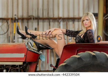 A blonde model posing in a barn environment