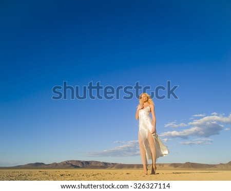 A blonde model posing in a desert environment  - stock photo