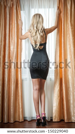 A blonde sensual woman in her black short dress and high heels  standing in front of the window.Beautiful blonde woman in black shinning dress. Luxury indoor scene with girl with long legs near window - stock photo