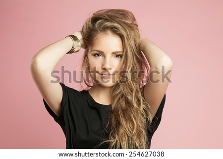 A blonde woman with beautiful curly hair and natural makeup in everyday clothes - stock photo