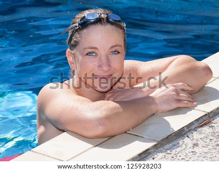 A blonde women relaxing on the edge of a pool . Friendly Smiling an looking traight in the camera.