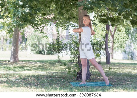 A blonde young woman doing yoga in park