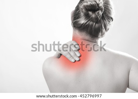 a blonde young woman with naked torso holds on hands in pain on the shoulder