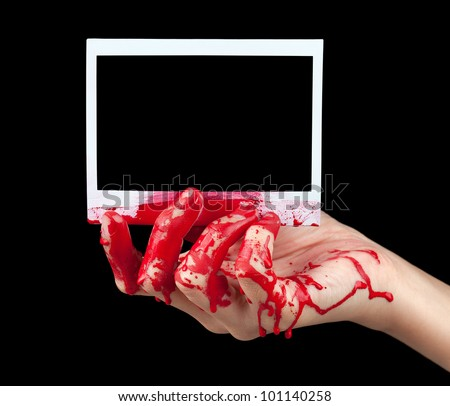 A blood covered hand holding up a piece of blank instant film isolated on black. - stock photo