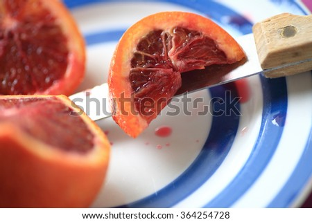 A blood orange with a section cut, resting on a knife on a blue-ringed dish - stock photo