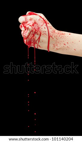 A bloody hand making a fist with blood dripping down isolated on black. - stock photo