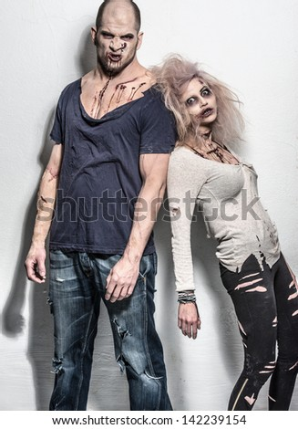 a bloody pair of scary evil zombies - stock photo