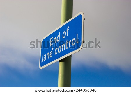 A Blue and white lane control sign, against a blue and cloudy sky. - stock photo