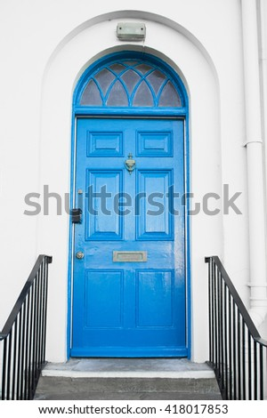 A blue arched door in a white town house