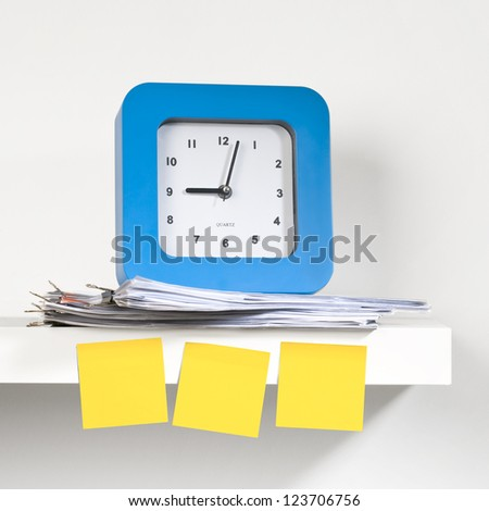 A blue clock placed on a shelf with documents. Sticky notes pasted on the clock. A reminder - concept.