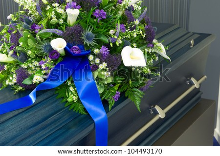 A blue coffin in a morgue with a flower arrangement - stock photo