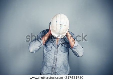 A blue collar worker is covering his ears - stock photo