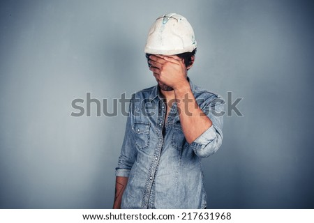 A blue collar worker wearing a hardhat is covering his face with his hands - stock photo