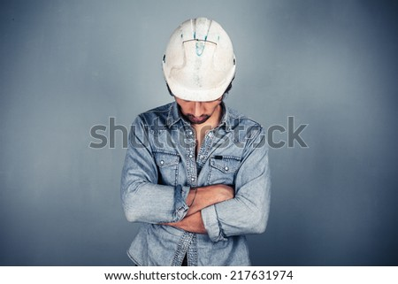A blue collar worker wearing a hardhat is standing with his arms crossed - stock photo