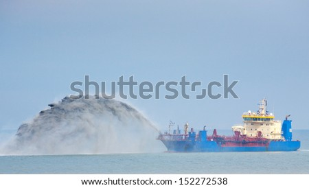 A blue dredging ship working in the North Sea. - stock photo