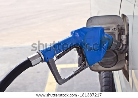 A blue fuel dispenser connecting to the car, add fuel, put in gasoline, benzene, diesel