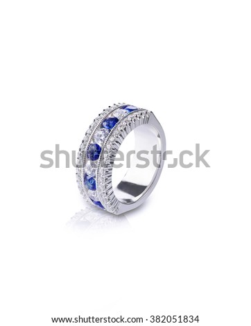 A blue Gemstone ring set in gold with diamonds. Isolated on white with a reflection. - stock photo