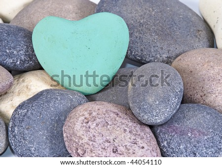 a Blue heart of stone between multi colored natural stones - stock photo