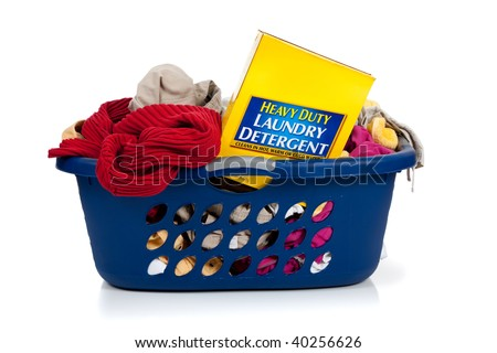 A blue laundry basket full of dirty clothes with laundry soap on a white background - stock photo