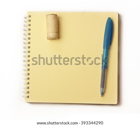 A blue pen and a wine cork on a yellow page of a spiral notebook, a photo of a notepad for tasting notes or a template for a wine-related announcement