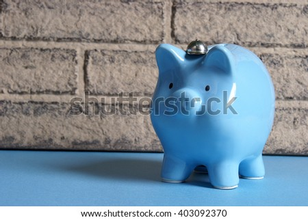 A blue pig bank rests up against a brick wall in this banking theme. - stock photo