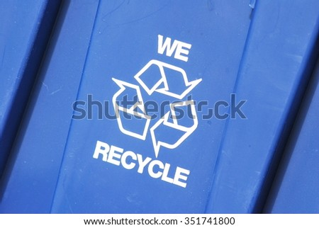 "A blue plastic container with the white universal recycling symbol that reads ""We recycle"" - stock photo"