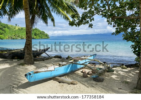 A blue polynesian outrigger that's still used today rests on the shore of a tropical island in Fiji - stock photo