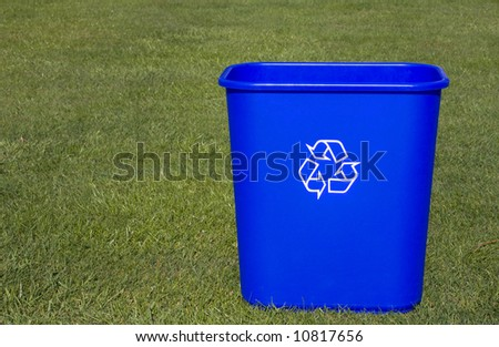A blue recycling box on a green lawn.