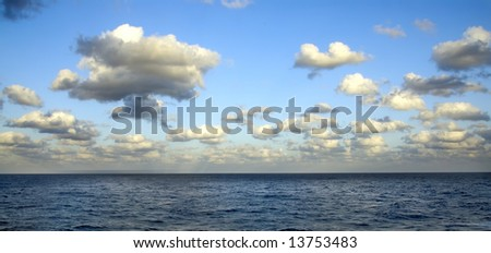 A blue sea with a sky full of white clouds