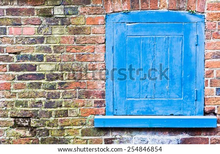 A blue shutter in a red brick wall - stock photo