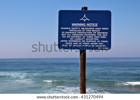 A blue sign warns against the possible danger of sharks at a beach.