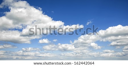 A blue sky and cloud background with white fluffy clouds to the horizon - stock photo