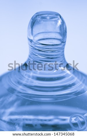 A blue toned close-up of a baby bottle teet