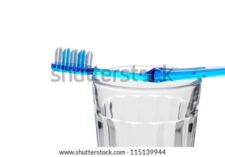 A blue toothbrush laying across the top of a water glass. Closeup in horizontal format on a white background.